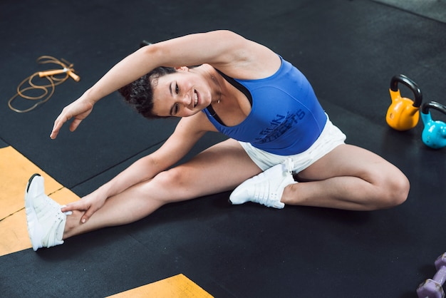 An athletic woman doing stretching exercise on floor in gym