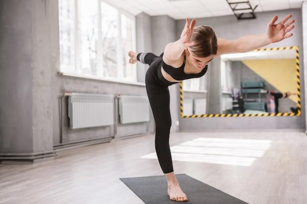 戦士のアーサナに立って、スポーツ スタジオでヨガをしている運動の女性