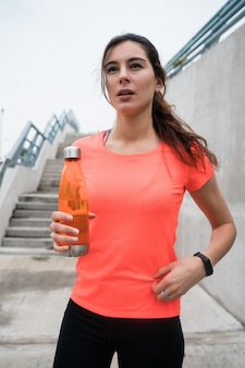 Athletic woman drinking water after training