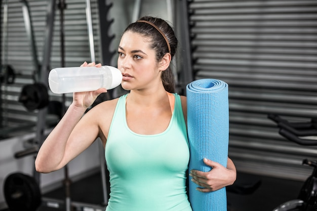 Athletic woman drinking water at crossfit gym