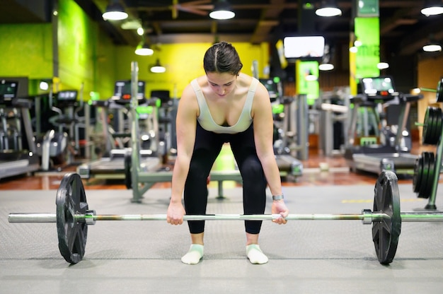 Athletic woman exercising deadlift in a gym.