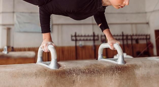 Donna atletica che si esercita sul cavallo con maniglie