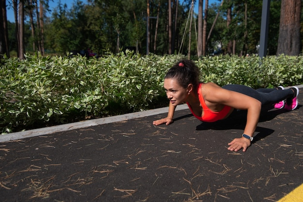Athletic woman exercising push-ups outdoor in the park.