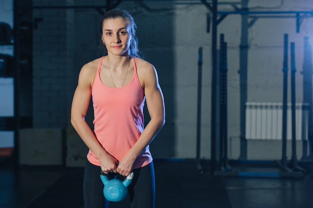 Athletic woman exercising with kettle bell while being in squat position.