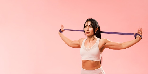 Athletic woman in gym outfit stretching resistance band