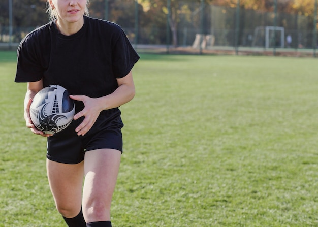 Athletic woman hands holding a rugby ball
