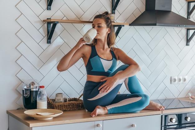 キッチンで朝食をとる運動女性、テーブルに座って飲んでいる女の子。
