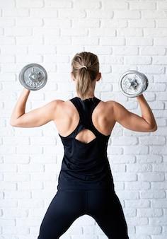 아령으로 그녀의 뒤와 팔 근육 훈련을 보여주는 검은 sportwear에 운동 여자
