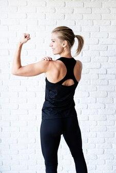 彼女の背中と腕の筋肉を示す黒いスポーツウェアの運動女性