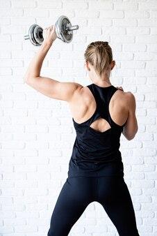 Спортивная (ый) женщина в черной спортивной одежде показывает мышцы спины и рук