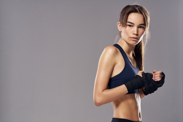 ボクシングの包帯の運動フィットネス戦闘機の明るい背景の運動の女性