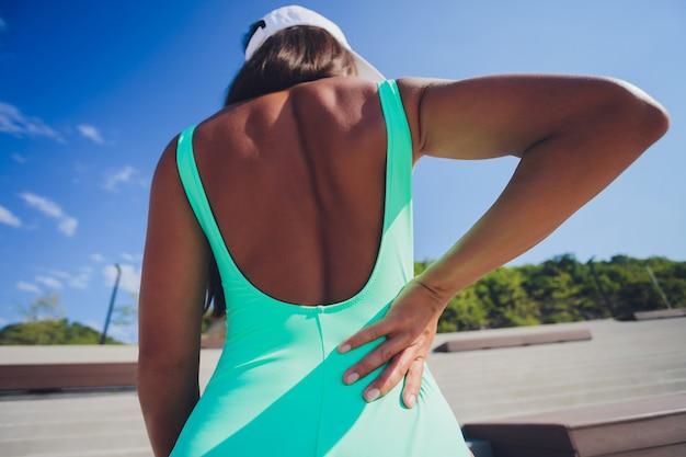 Спортивная женщина в розовой спортивной одежде стоит на берегу моря, потирая мышцы нижней части спины