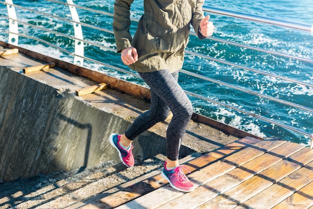 スポーツ服を着て運動女性が海を背景にスニーカーで階段を駆け上がる