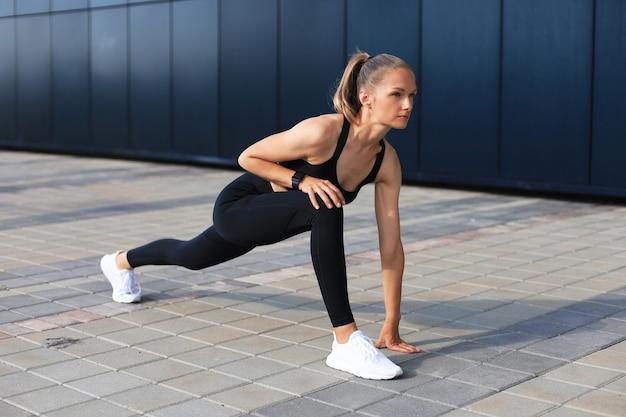 야외에서 달리는 동안 출발선에 서 있는 스포츠 의류를 입은 운동 여성.