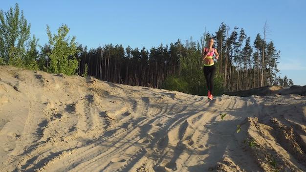 砂の上を屋外で走っているスポーツユニフォームの運動女性