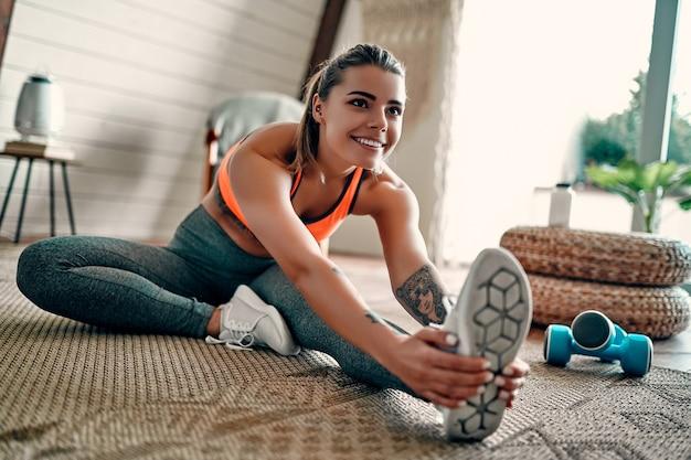 거실에서 집에서 피트니스 스트레칭 운동을 하는 운동복을 입은 운동 여성. 스포츠 및 레크리에이션 개념입니다.