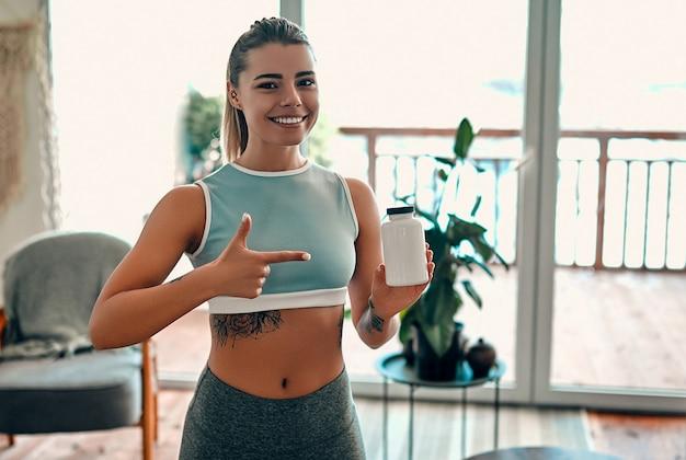 Спортивная женщина в спортивной одежде держит в руке банку с протеином и показывает жест пальцем дома в гостиной. концепция спорта и отдыха.