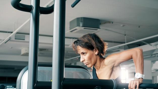 운동복을 입은 운동 여성이 체육관에서 평행봉에서 팔굽혀펴기를 하고 있습니다. 스포츠 및 보디 빌딩 개념, 톤.