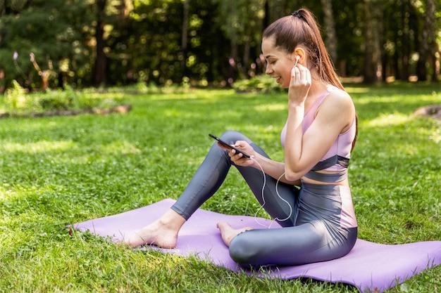 Спортивная женщина в спортивной одежде смотрит на экран мобильного телефона