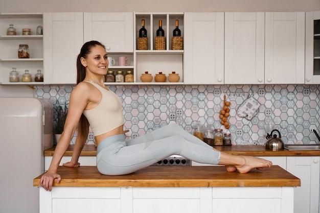 軽くてモダンなキッチンのテーブルの上でポーズをとるスポーツウェアのアスリート女性。美しさ、健康、適切な栄養の概念。