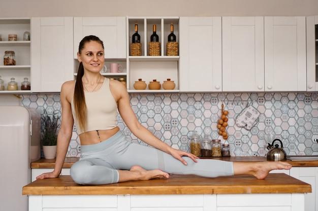 Спортивная (ый) женщина в спортивной одежде позирует на столешнице светлой современной кухни. понятие красоты, здоровья, правильного питания.