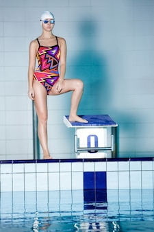 スイミングプールで水泳レースを開始する準備ができて水泳帽と眼鏡の運動選手