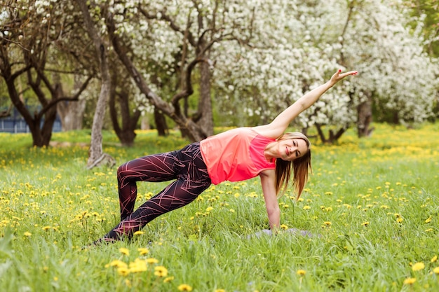 Athletic woman is doing side plank outdoors in the park among blooming trees in spring
