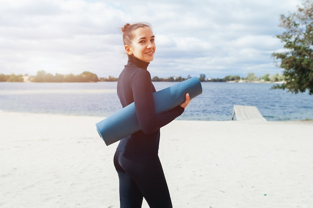 An athletic woman is standing with her back to the camera