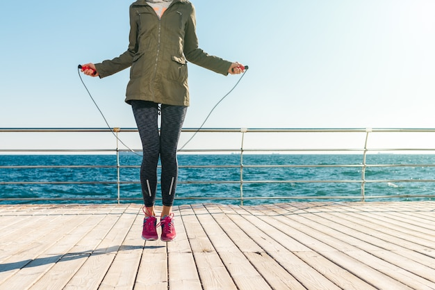 Athletic woman in a jacket and sneakers jumps rope in the morning on the background of the sea