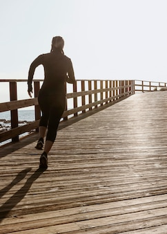 Athletic woman jogging by the beach with copy space