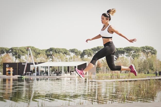 Спортивная (ый) женщина прыгает в парке