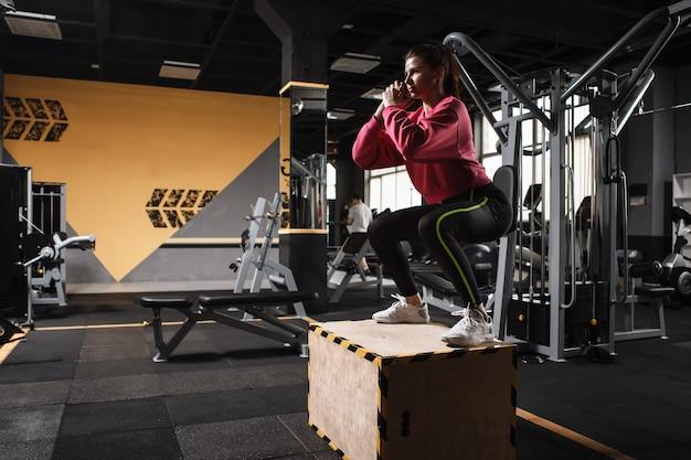 ジムでボックスにジャンプする運動の女性