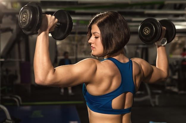 ジムでダンベルを持ち上げる運動の女性