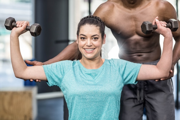 Athletic woman lifting weights helped by trainer at gym