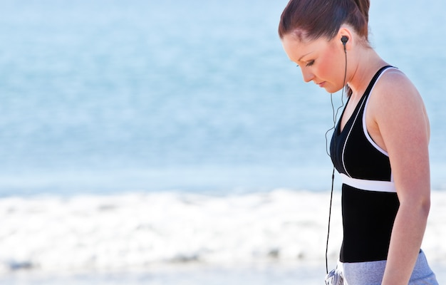 Athletic woman listening music on the beach