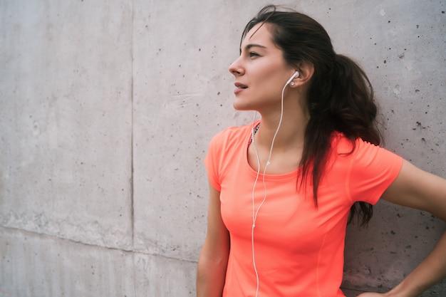 トレーニングからの休憩時間に音楽を聴くスポーツの女性
