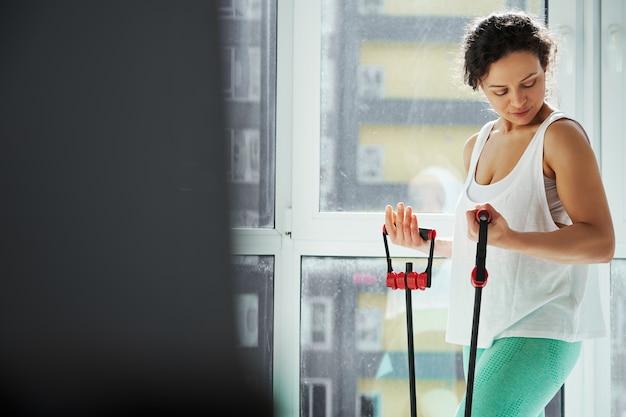 피트니스 하네스와 함께 운동하는 동안 그녀의 팔뚝을보고 운동 여자