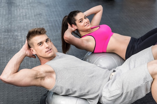 Athletic woman and man doing crunches at gym
