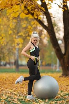 Donna atletica che misura la sua vita