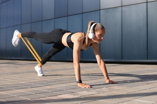 판자 위치에 있는 운동 여성은 피트니스 껌을 사용합니다.