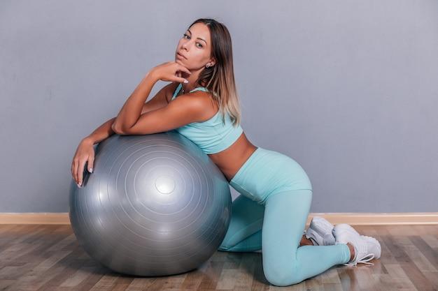 スタジオボディービルダーでポーズをとる運動女性筋肉のセクシーな体と強い筋肉黒で撮影