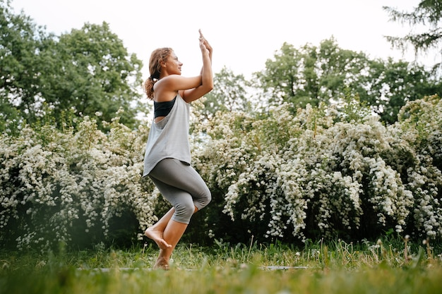 Athletic woman practices yoga and stands on one leg on a yoga mat in the park eka pada utkatasana pose