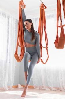Спортивная (ый) женщина, практикующая летать в гамаке йоги в тренажерном зале с концепцией здравоохранения в стиле буддийского холла
