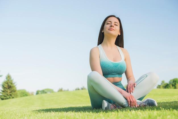 Атлетическая напольная практикуя йога женщины