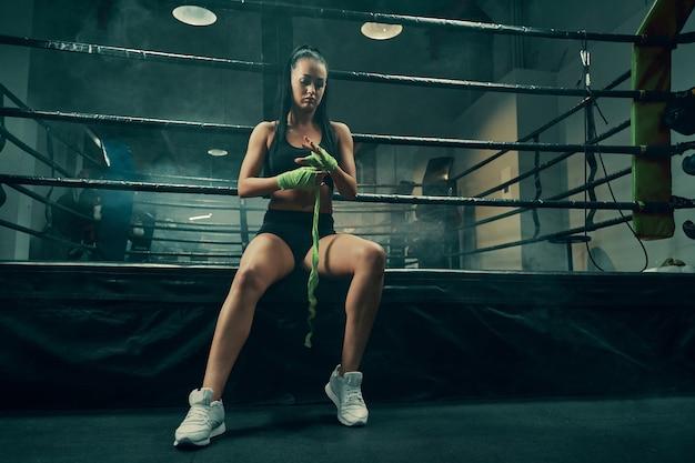 ボクシングの戦いの準備をし、ボクシングのリングの側面に座っている手に包帯を巻く運動の女性