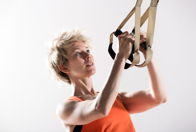 Athletic woman pulling fitness cords