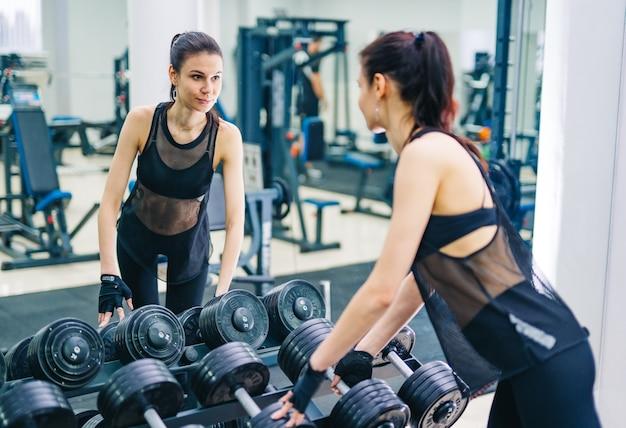ダンベルで筋肉をポンピングする運動女性。スポーツ、フィットネス、健康的なライフスタイルのコンセプト。