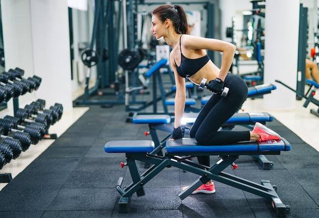 Спортивная (ый) женщина накачивает мышцы с гантелями. концепция спорта, фитнеса и здорового образа жизни.