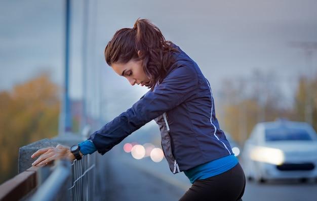 Спортивная женщина отдыхает после пробежки и опирается на парапет моста