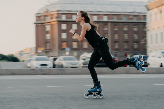 Athletic woman rides on rollers moves very fast dressed in active wear enjoys rollerblading being photographed in action poses at urban place engaged in extreme sport. active lifestyle concept